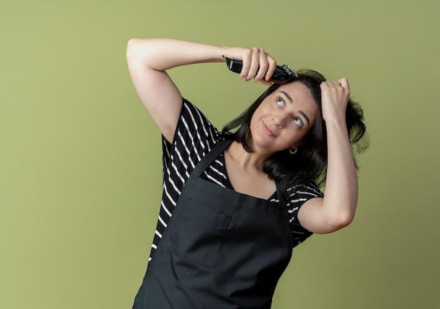 Młoda piękna kobieta fryzjerka w fartuchu trzymając maszynę do cięcia włosów będzie ściąć włosy na światło
