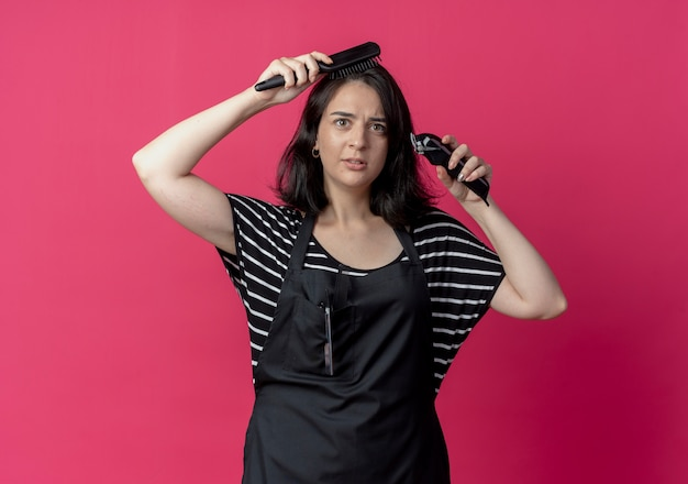 Młoda piękna kobieta fryzjerka w fartuchu trzymając maszynę do strzyżenia włosów czesanie jej włosy szczotką stojącą na różowej ścianie