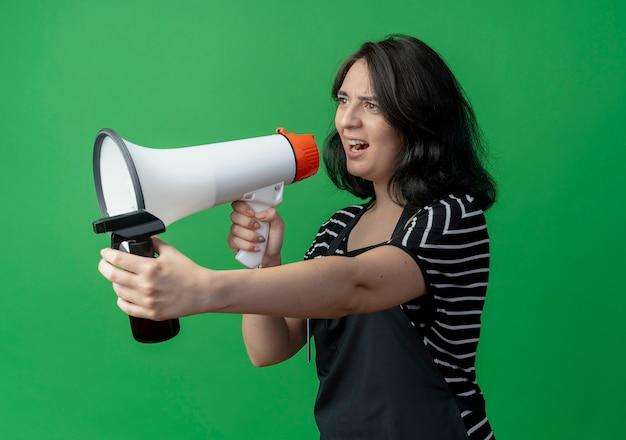 Młoda piękna kobieta fryzjerka w fartuchu trzymając spray krzycząc do megafonu z agresywnym wyrazem stojącym nad zieloną ścianą