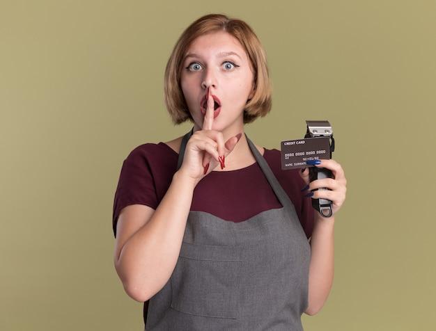Młoda piękna kobieta fryzjerka w fartuchu trzymająca trymer i kartę kredytową wykonująca gest ciszy z palcem na ustach wyglądająca na zaskoczoną stojącą nad zieloną ścianą
