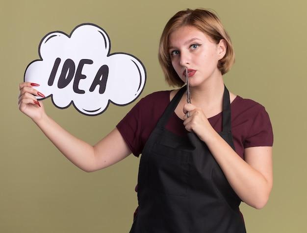 Młoda piękna kobieta fryzjerka w fartuchu z nożyczkami pokazuje znak bańki mowy z pomysłem na słowo patrząc z przodu z pewnym siebie wyrazem twarzy na inteligentnej twarzy stojącej nad zieloną ścianą