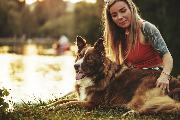 Młoda piękna kobieta głaszcząca swojego uroczego psa w parku