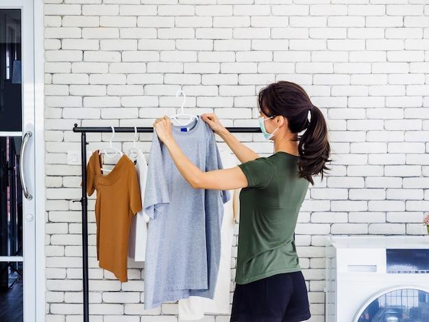 Młoda piękna kobieta, gospodyni domowa w swobodnym noszeniu ochronnej maski na twarz, wiszącej suchej koszuli z wieszakiem na sznurku po praniu w pobliżu pralki w pralni na białej ścianie.