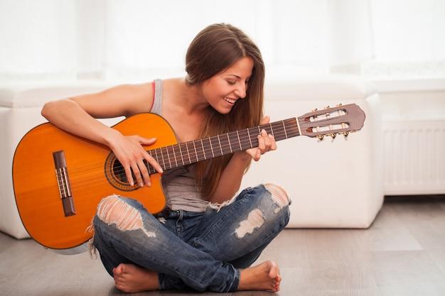 Młoda piękna kobieta gra na gitarze