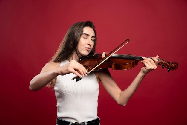 Młoda piękna kobieta gra na skrzypcach