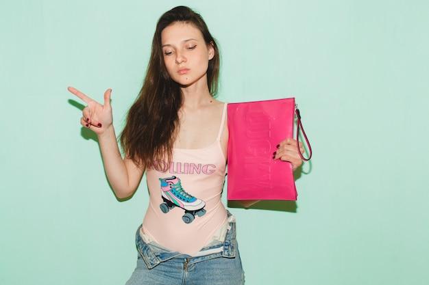 Młoda piękna kobieta hipster pozowanie na niebieskiej ścianie, trzymając w ręku różowe modne sprzęgło