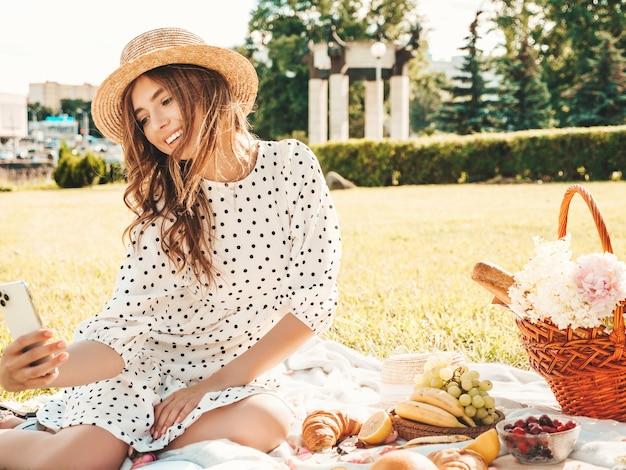 Młoda piękna kobieta hipster w modne letnie dżinsy, różowy t-shirt i kapelusz. beztroska kobieta robi piknik na zewnątrz.