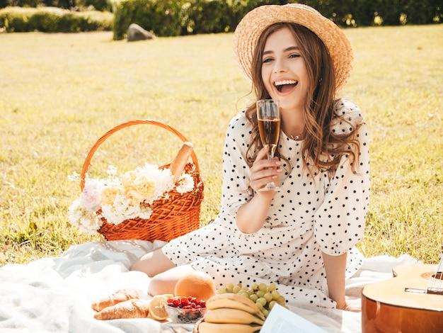 Młoda piękna kobieta hipster w modnej letniej sukience i kapeluszu. beztroska kobieta robi piknik na zewnątrz.