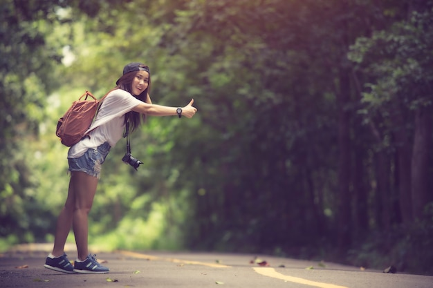 Młoda piękna kobieta hitchhiking pozycję na drodze.