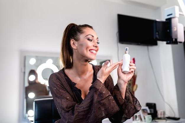 Młoda piękna kobieta i profesjonalna piękność tworzą vlogerkę lub blogerkę, która nagrywa samouczek makijażu do udostępnienia na stronie internetowej lub w mediach społecznościowych.