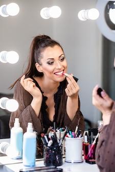 Młoda piękna kobieta i profesjonalna uroda makijażystka vlogerka nagrywa samouczek makijażu do udostępnienia na stronie internetowej lub w mediach społecznościowych