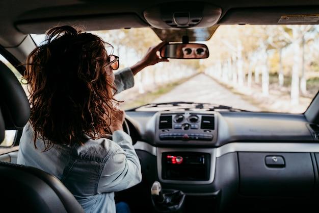 Młoda piękna kobieta jedzie furgonetką ścieżką drzewa. koncepcja podróży, widok od wewnątrz