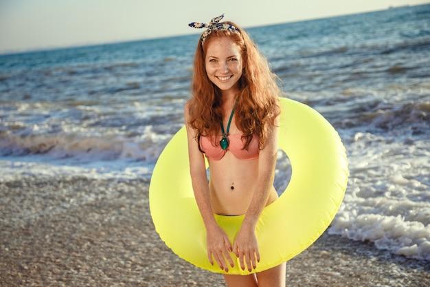 Młoda piękna kobieta jest relaks w zachód słońca plaża z gumowym pierścieniem.