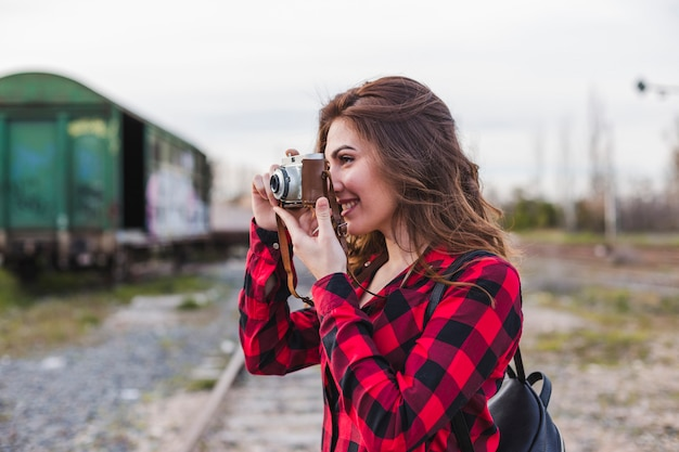 Młoda piękna kobieta jest ubranym przypadkowych ubrania bierze obrazek z rocznik kamerą.