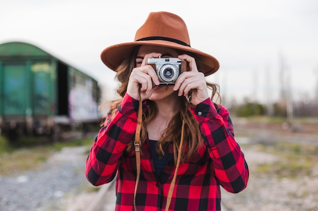 Młoda piękna kobieta jest ubranym przypadkowych ubrania i modnisia kapelusz bierze fotografię z rocznika kamerą
