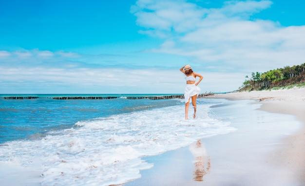 Młoda piękna kobieta jest ubranym słomianego kapelusz, biały strój kąpielowy i spódnicę pozuje biegający wzdłuż kipieli linii na plażowych pobliskich fala.