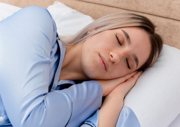 Młoda piękna kobieta kłaść na łóżku w niebieskiej piżamie