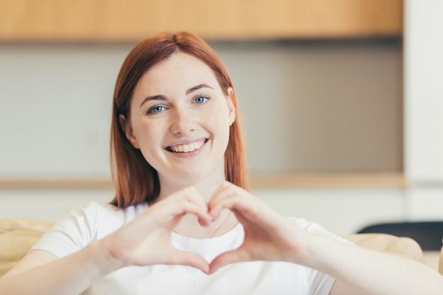 Młoda piękna kobieta komunikuje się przez wideo, siedząc w domu na kanapie, pokazując znak serca rękami
