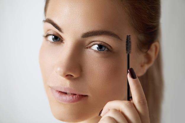 Młoda piękna kobieta korygująca kształt brwi. konturowy makijaż brwi .