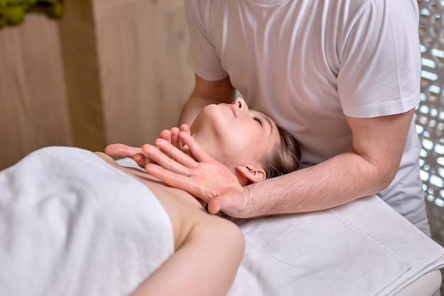 Młoda piękna kobieta korzystająca z masażu twarzymężczyzna terapeuta wykonujący masaż głowy i szyi kobiecemu klientowi