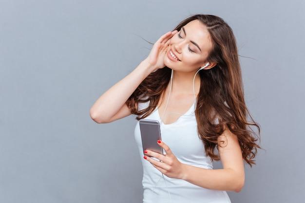 Młoda Piękna Kobieta Korzystająca Ze Smartfona I Słuchająca Muzyki Na Szarym Tle Premium Zdjęcia