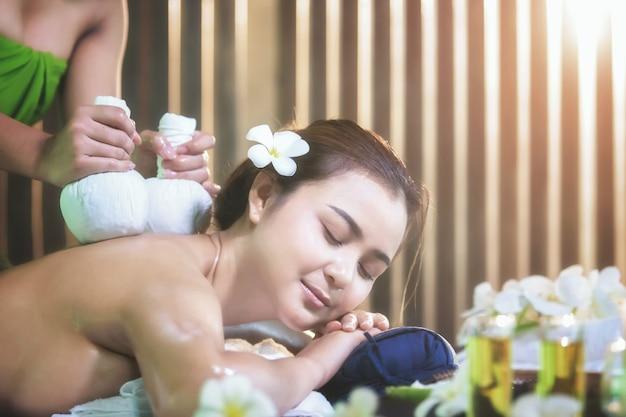 Młoda piękna kobieta korzystających masaż w salonie spa, spa masaż ciała kobieta ręce leczenia
