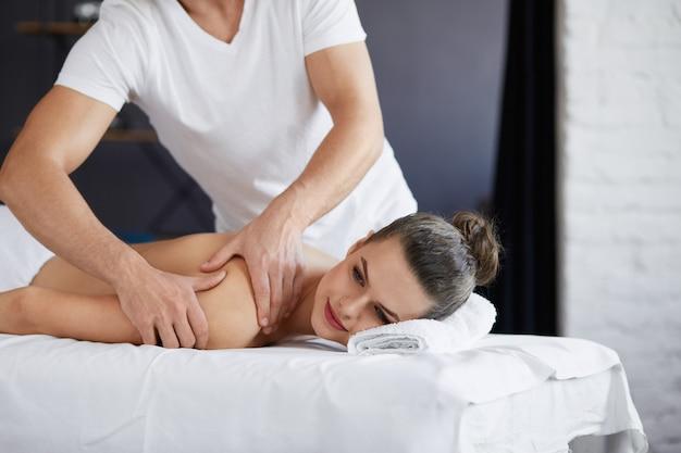 Młoda piękna kobieta korzystających z masażu pleców i shouders w spa. profesjonalny terapeuta leczy pacjentkę w mieszkaniu. koncepcja relaksu, piękna, ciała i twarzy. masaż domowy