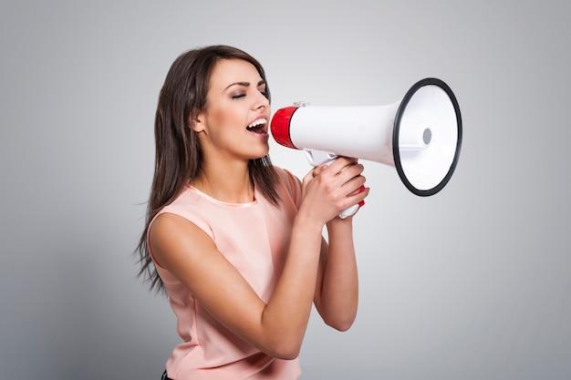 Młoda piękna kobieta krzyczy przez megafon