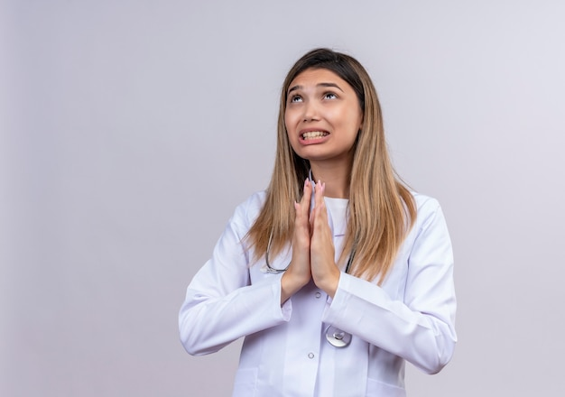 Młoda piękna kobieta lekarz ubrana w biały fartuch ze stetoskopem błagając i modląc się rękami wraz z wyrazem nadziei na twarzy bardzo emocjonalny i zmartwiony