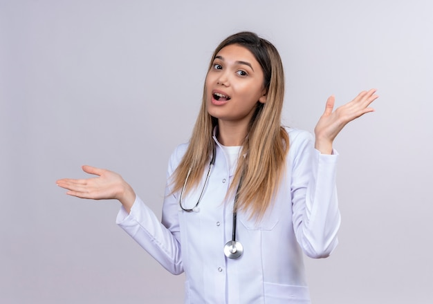 Młoda piękna kobieta lekarz ubrana w biały fartuch ze stetoskopem, patrząc niepewnie i zdezorientowana, rozkładając dłonie mając wątpliwości