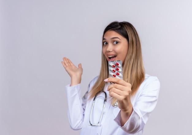 Młoda piękna kobieta lekarz ubrana w biały fartuch ze stetoskopem, trzymając blister z pigułkami, uśmiechając się radośnie, przedstawiając ramieniem jej dłoni