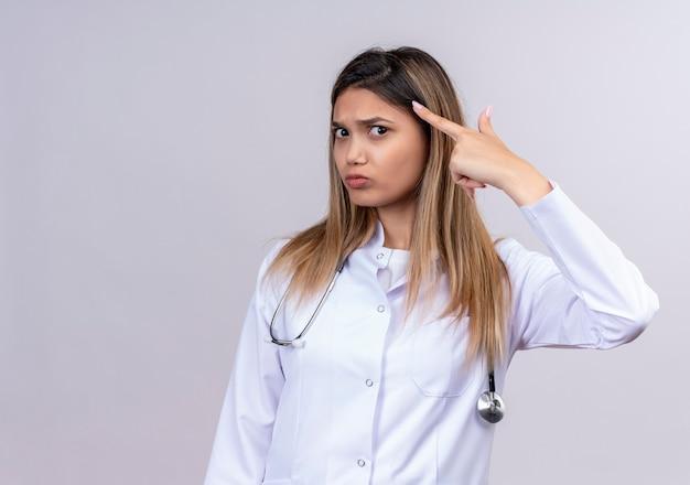 Młoda piękna kobieta lekarz ubrana w biały fartuch ze stetoskopem wskazując świątynię palcem mocno koncentrując się na idei z poważnym wyrazem twarzy