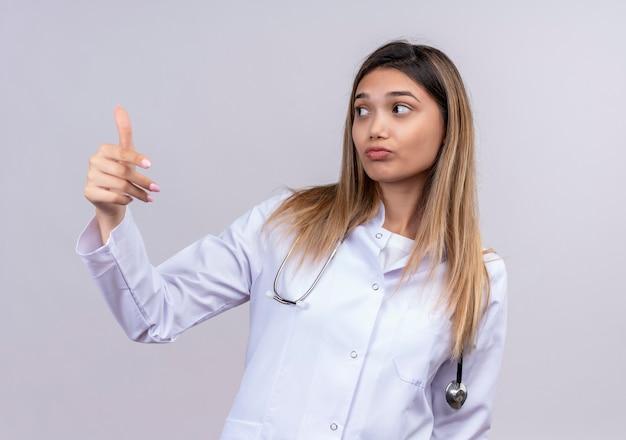 Młoda piękna kobieta lekarz ubrany w biały fartuch ze stetoskopem patrząc na bok robi w geście ręką