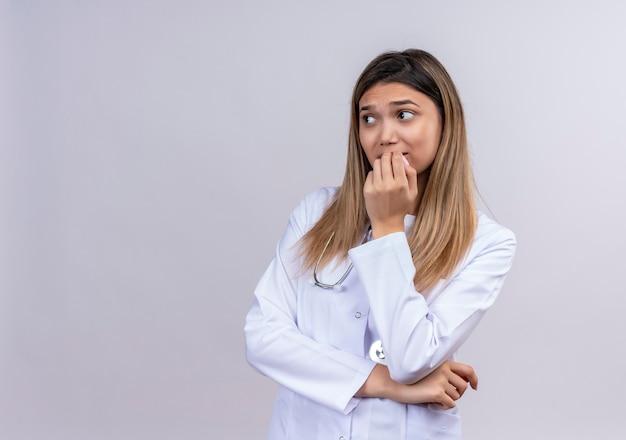 Młoda piękna kobieta lekarz ubrany w biały fartuch ze stetoskopem, patrząc na bok zestresowany i nerwowy obgryzanie paznokci