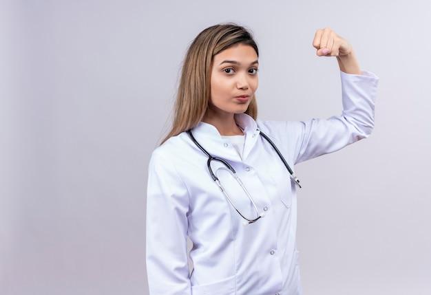 Młoda piękna kobieta lekarz ubrany w biały fartuch ze stetoskopem, patrząc pewnie podniesionej pięści, udając zwycięzcę