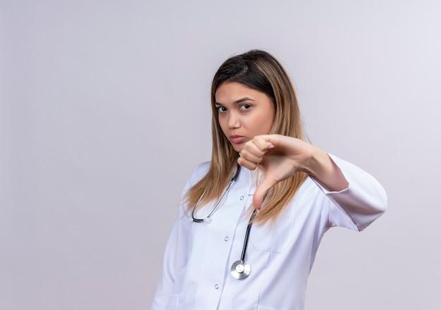 Młoda piękna kobieta lekarz ubrany w biały fartuch ze stetoskopem, patrząc z marszczącą brwią twarz pokazującą niechęć