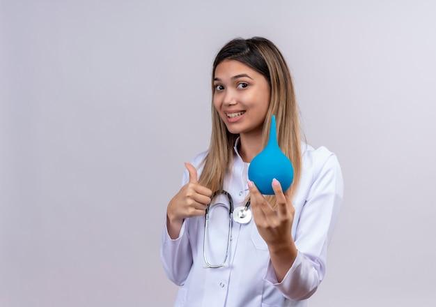 Młoda piękna kobieta lekarz ubrany w biały fartuch ze stetoskopem trzymając lewatywę uśmiechnięty pokazując kciuk do góry