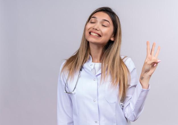 Młoda piękna kobieta lekarz ubrany w biały fartuch ze stetoskopem z zamkniętymi oczami, uśmiechając się radośnie, pokazując numer trzy palcami
