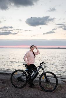 Młoda piękna kobieta, lekkoatletka z rowerem, od rana patrzy na świt nad morzem i odpoczywa od przejażdżki rowerem.