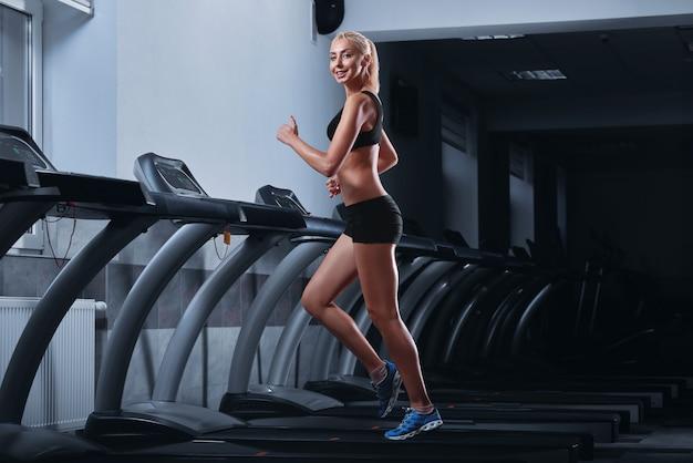 Młoda piękna kobieta lekkoatletycznego działa na bieżni na siłowni