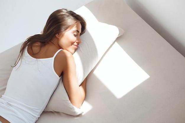Młoda piękna kobieta, leżąc na łóżku wcześnie rano