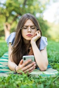 Młoda piękna kobieta, leżąc na trawie, czytając wiadomość na telefon komórkowy w parku