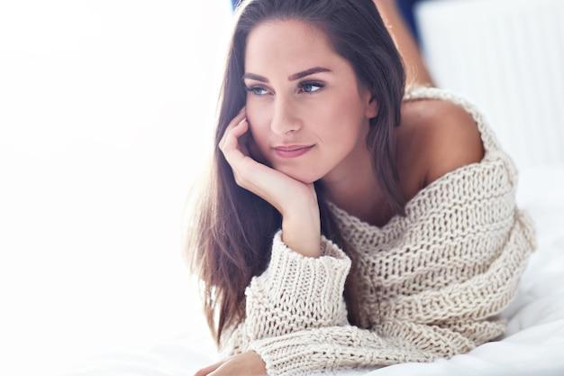 Młoda piękna kobieta leżąca rano na łóżku