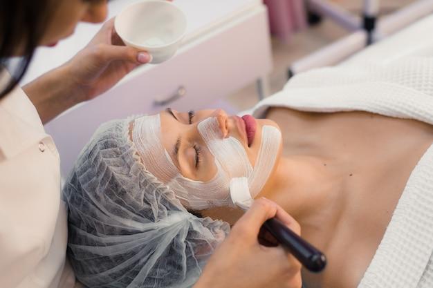 Młoda piękna kobieta ma zdrój procedurę na jej twarzy