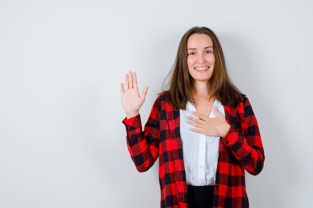 Młoda piękna kobieta macha ręką na powitanie, z ręką na klatce piersiowej w swobodnym stroju i patrząc pozytywnie, widok z przodu.