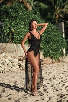 Młoda piękna kobieta moda na sobie strój kąpielowy i czarną pelerynę plażową koronki pozostaje w lecie na ośrodek