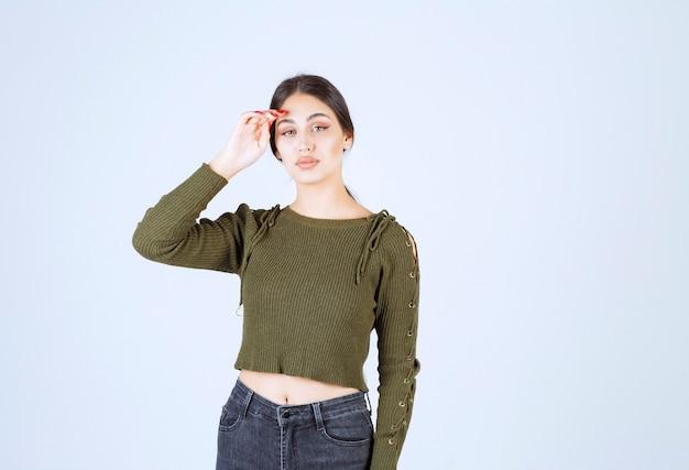 Młoda piękna kobieta model stojący i dotykając czoła.