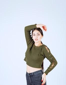 Młoda piękna kobieta model stojący i pozowanie na białej ścianie.