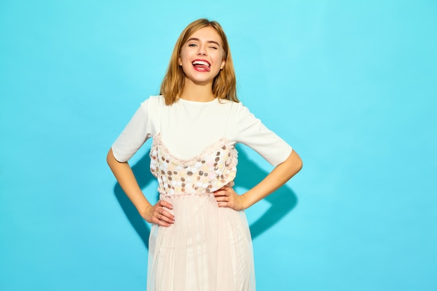 Młoda piękna kobieta. modna kobieta w mrugnięciu letnie ubrania. śmieszny model odizolowywający na błękit ścianie
