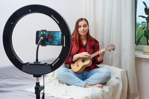 Młoda piękna kobieta muzyk nagrywa transmisję wideo na deathphone. zdalne lekcje muzyki. koncert online.
